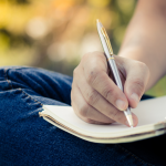 man writing notebook outdoor