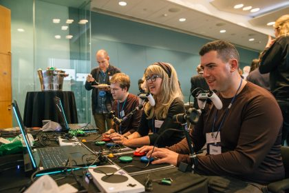 Julie Elsden and James Carr sitting next to each other with their chins positioned on games console controllers, using their chins to navigate and play a video game.