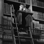 black and white man sitting reading in old grand library