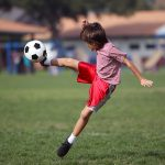 Boy kicking soccer in the park - Authentic action with soccer ball - copy space - landscape format