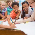 group of children writing with teacher