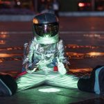 Child astronaut sitting on a green light