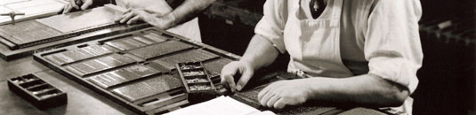 A black and white photo of a printing press at work
